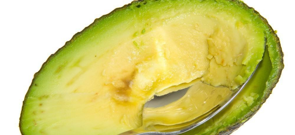 A spoon being used to scrape the inside of an avocado.