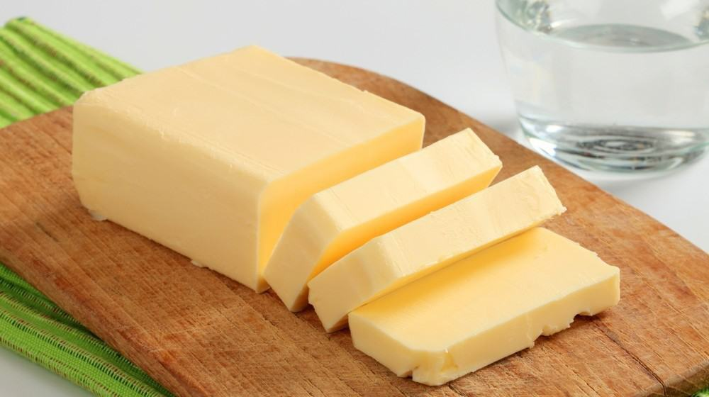 A block of butter on a wooden surface, with a few slices separated from the the main block.