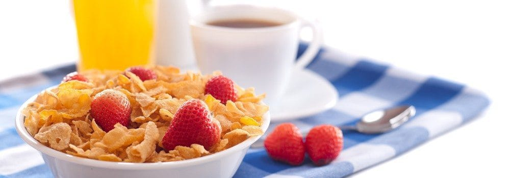 A bowl of cereal with raspberries, next to a cup of coffee and orange juice.