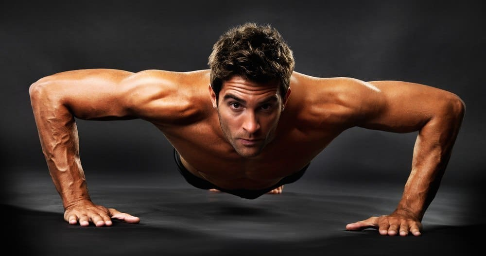 A muscular man performing a push-up in front of a camera.