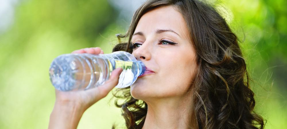 A woman taking a sip of bottled water.