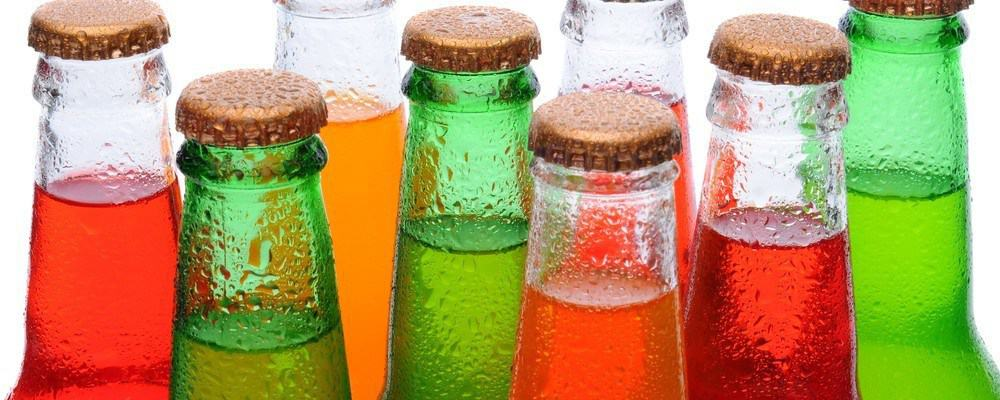 Soda bottles with various colored liquids in them.