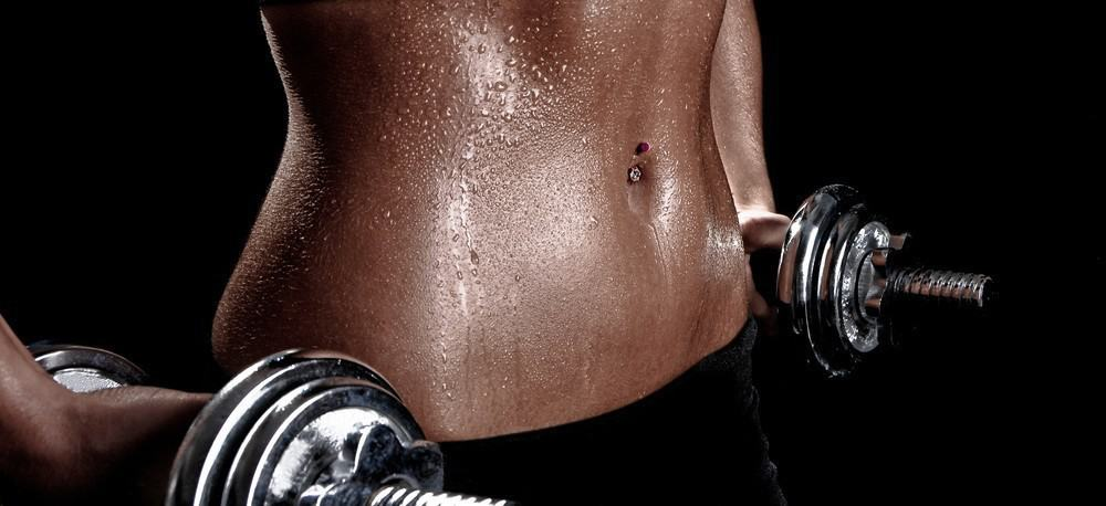 A fit woman sweaty torso during a workout.