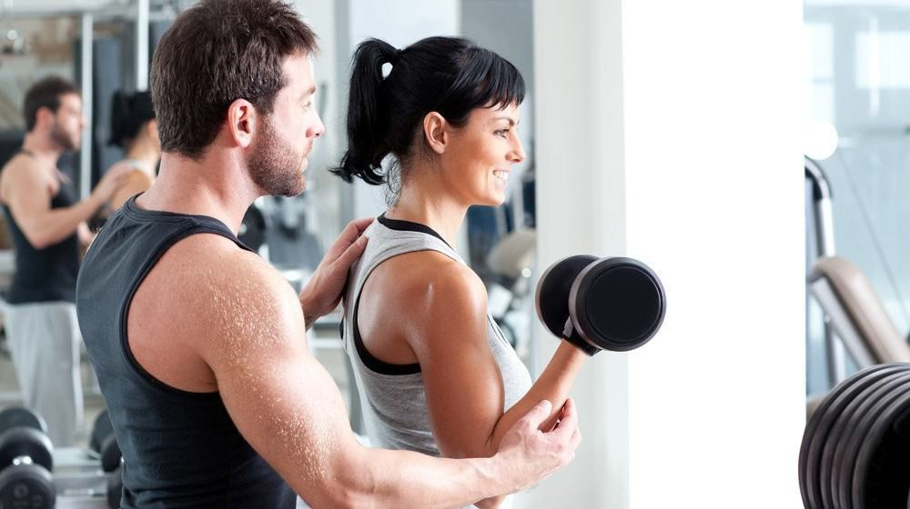 A trainer helping a woman with a dumbbell exercise.