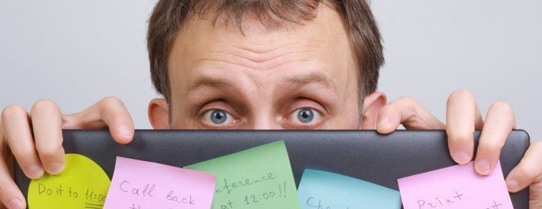 Stressed person looking at camera from behind a wall of sticky notes.