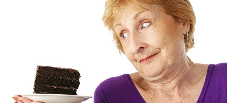 An elderly woman looking at a slice of chocolate cake with a dubious expression.