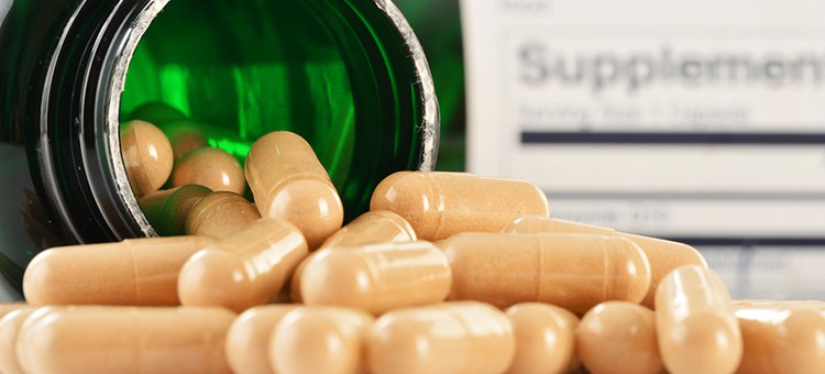 Supplement pills in front of a bottle.