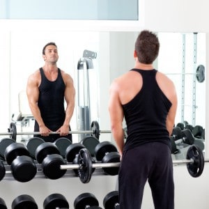Muscular man lifting weights in front of a gym mirror.