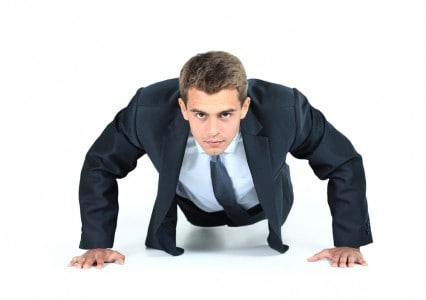 Businessman performing push ups.