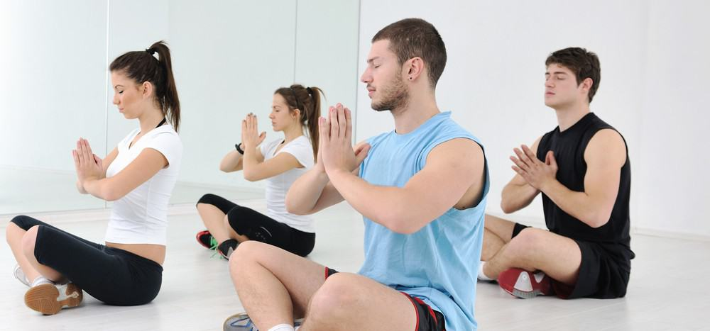 A group of people performing a meditative yoga pose.