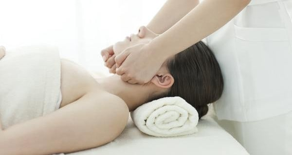 A woman receiving a jaw massage.
