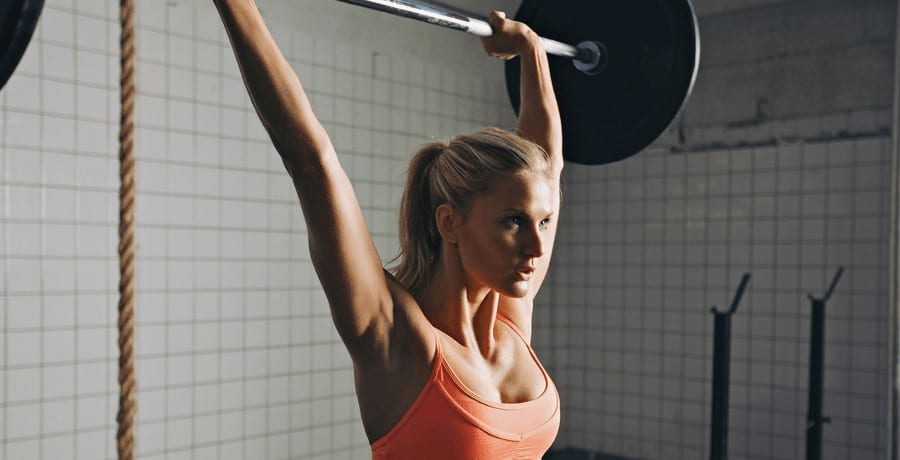 A woman lifting a barbell.