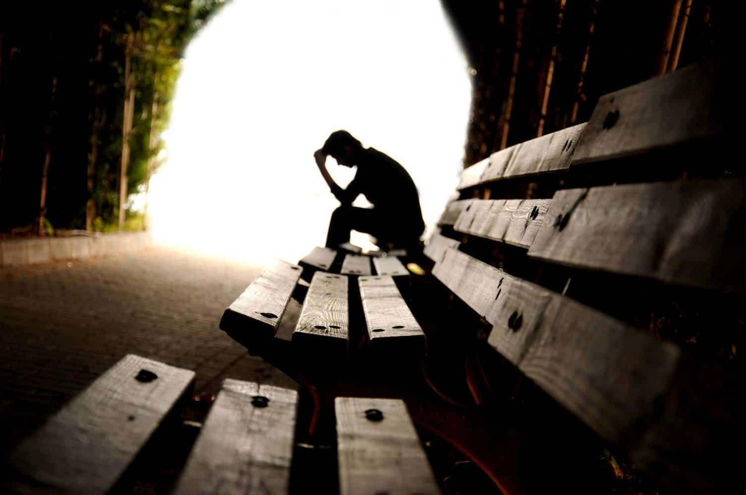 A depressed person sitting at a bench.