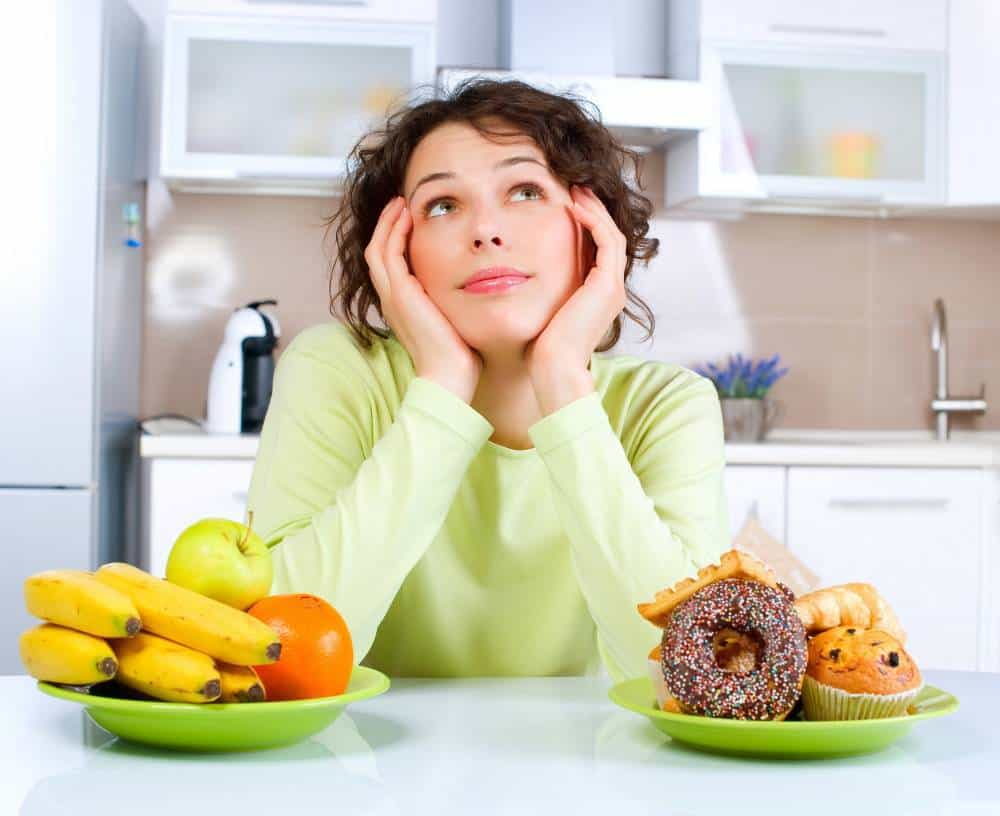 A woman sitting between a bowl of fruit and a bowl of desserts, thinking.