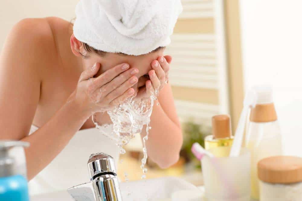 A woman cleaning her face at the sink.