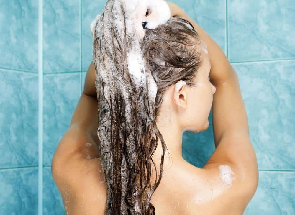 A woman washing her hair with shampoo.