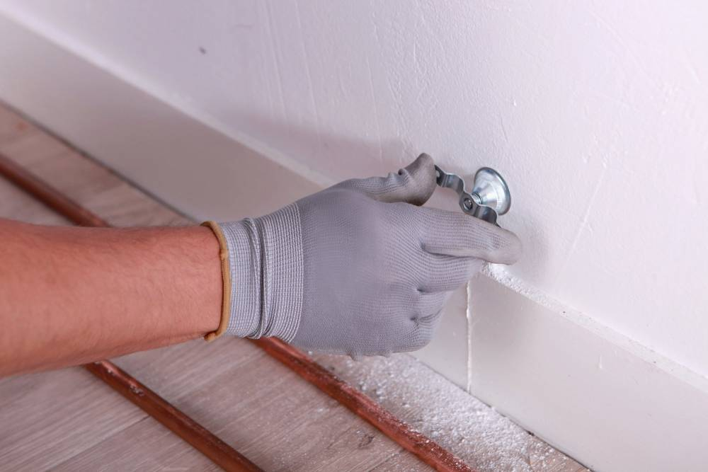 A person sealing cracks in the wall.