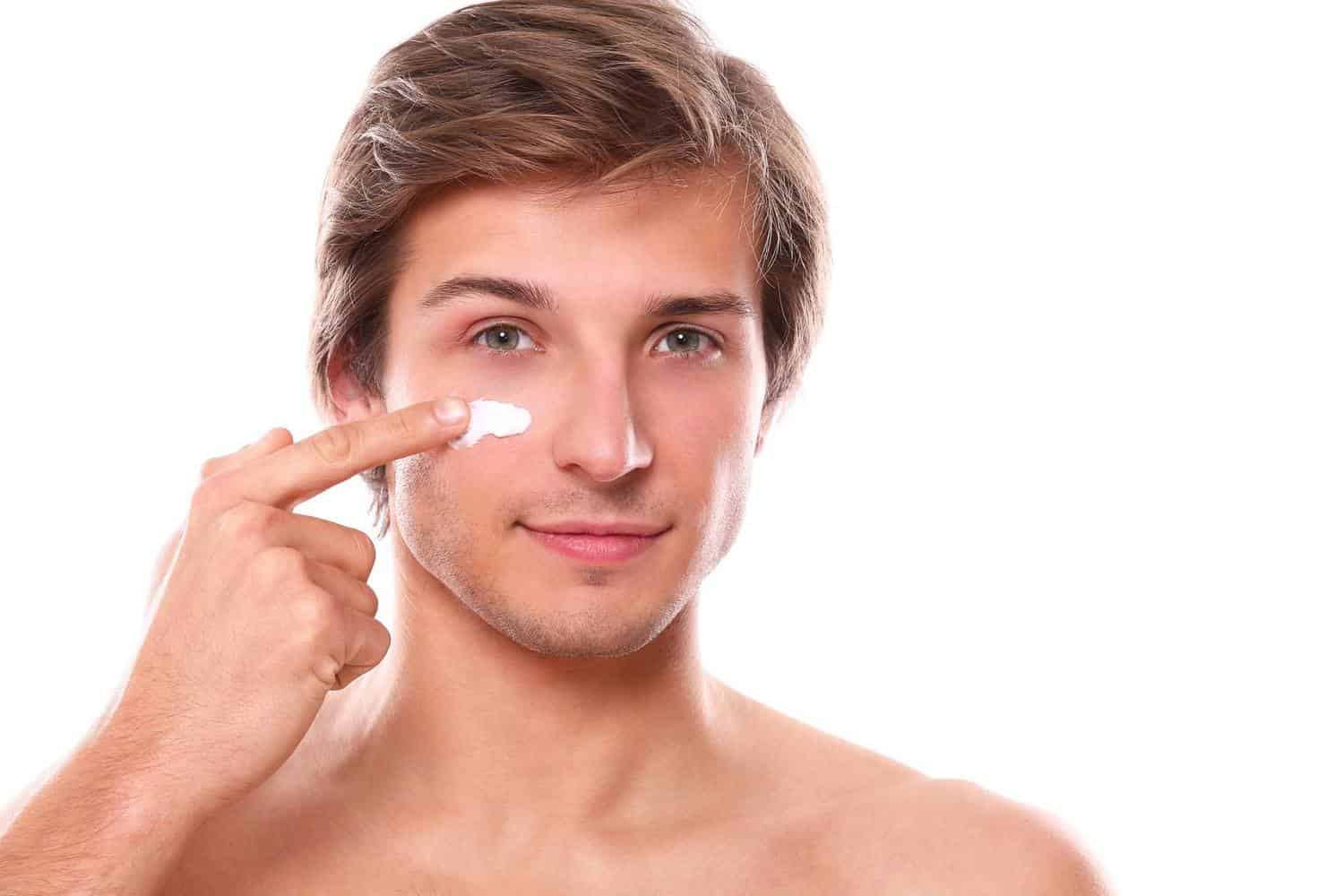A man putting a line of toothpaste or cream on his face.