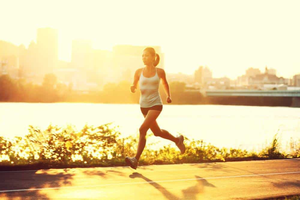 A woman running along a body of water in an urban sunset.