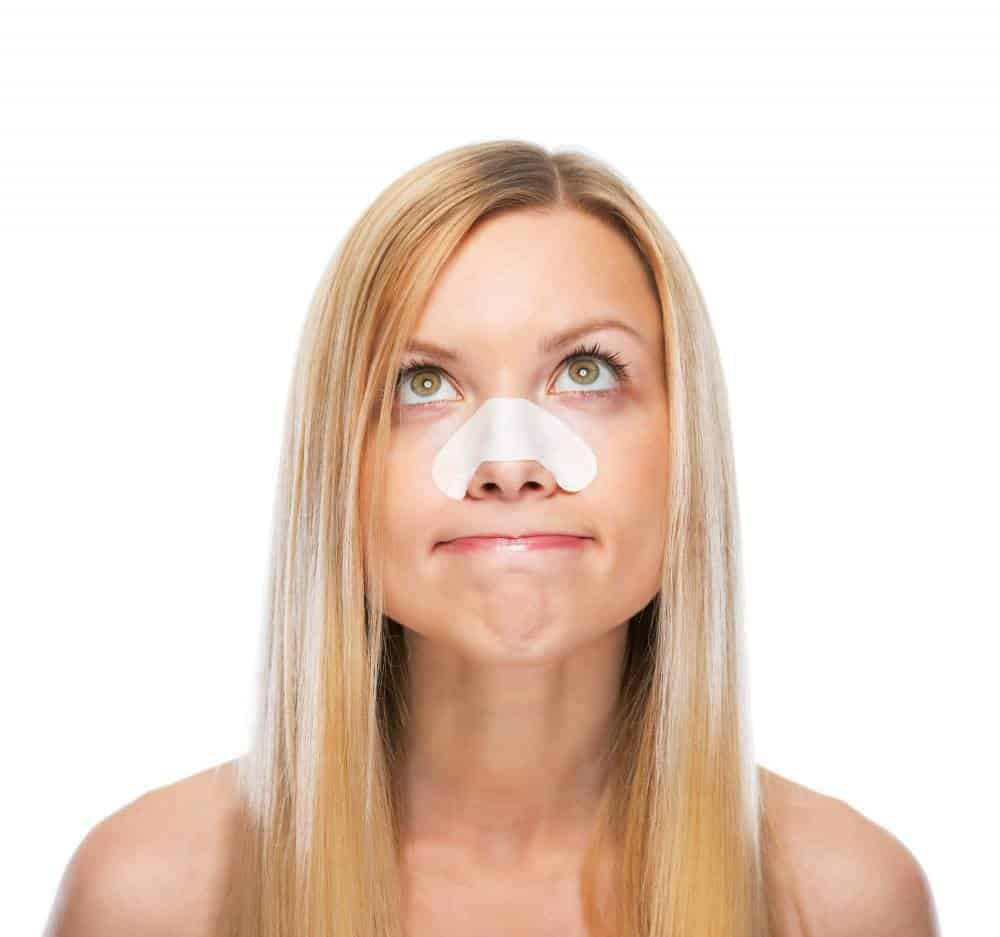 A woman using a sticker on her nose to remove acne.