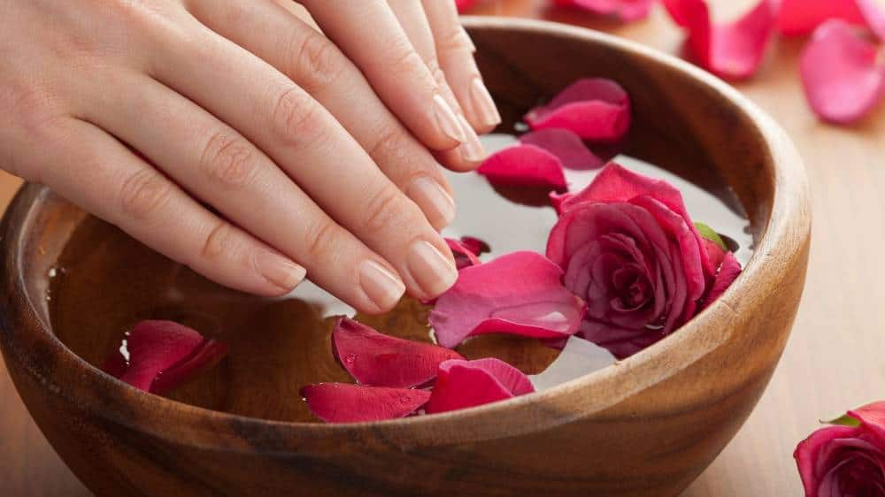 A person soaking their nails in rose water.