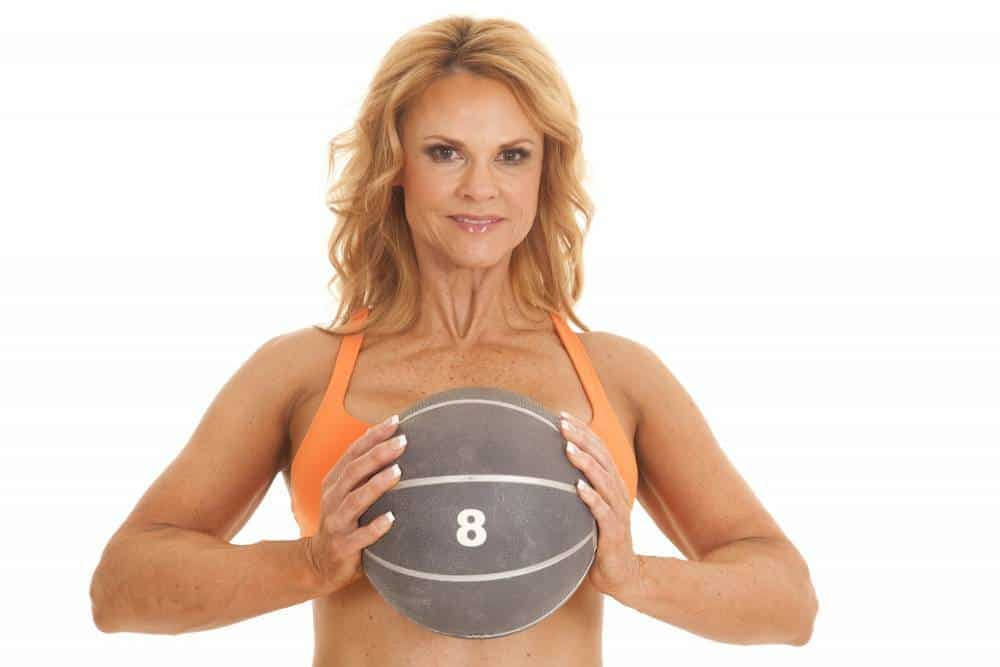 A woman performing the chest squeeze with a basketball.
