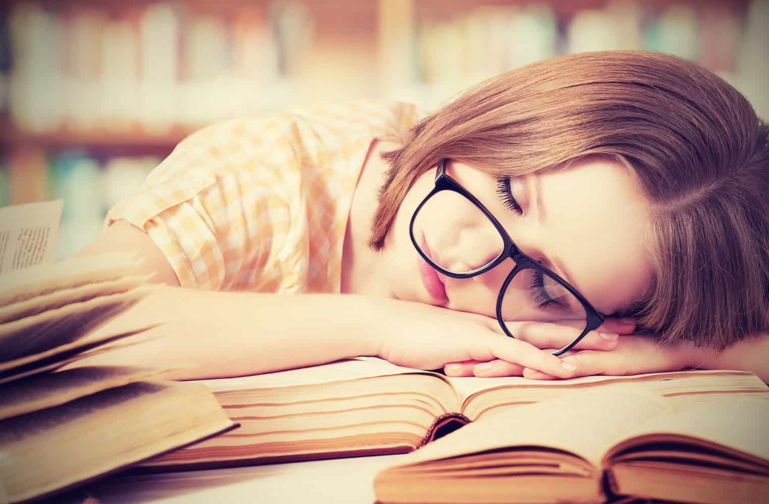 A woman sleeping in a library.