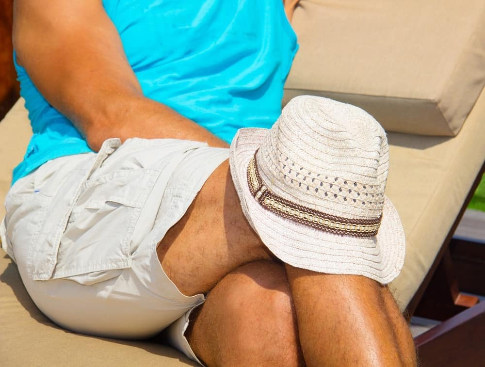A person in the sun covering their knee with a hat.