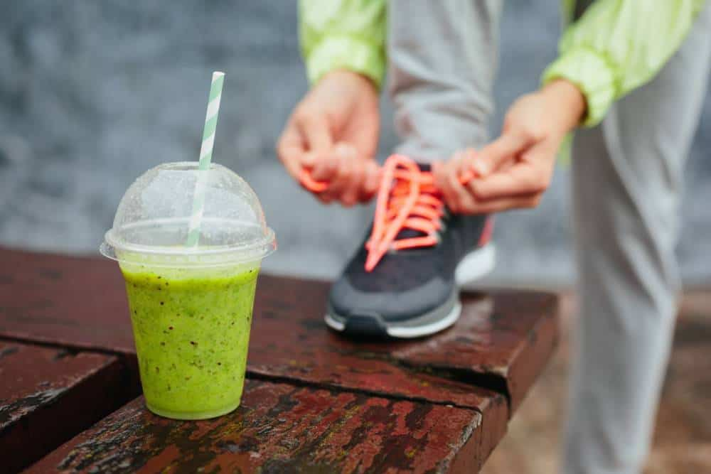 Green shake next to a person tying their shoe laces.