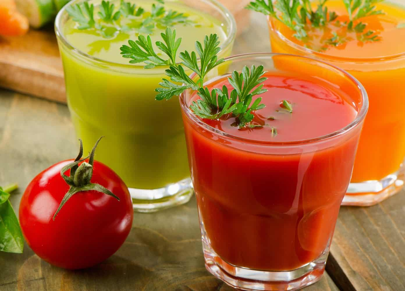 Glasses of green and red tomato juice.