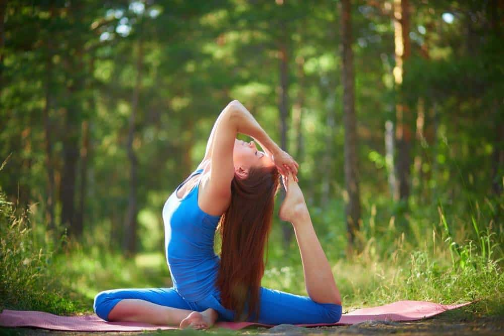 A woman doing yoga in a forest.