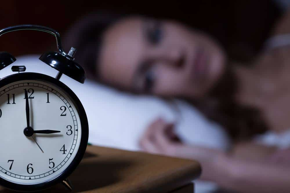 A sleepless woman looking at her alarm clock.