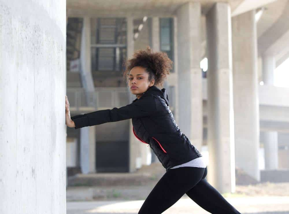 A woman stretching at a wall in an urban environment.