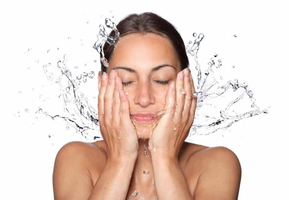 A woman splashing water on her face.