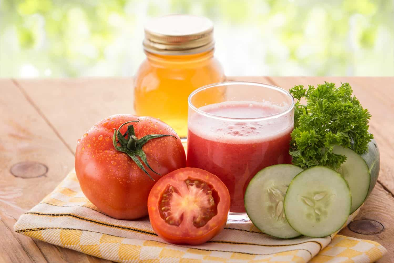A glass of tomato juice with some tomatoes, cucumbers and a glass of liquid