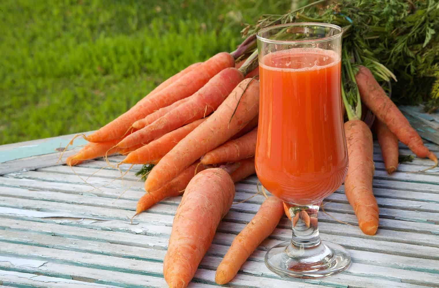 A carrot sticks surrounding a glass of carrot juice.