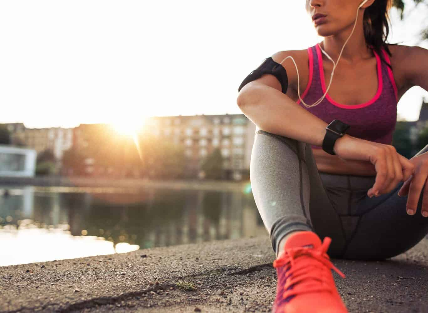 A fit woman resting after a run in an urban environment.