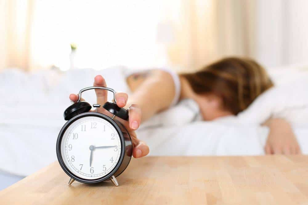 A woman pushing her alarm clock while getting out of bed.