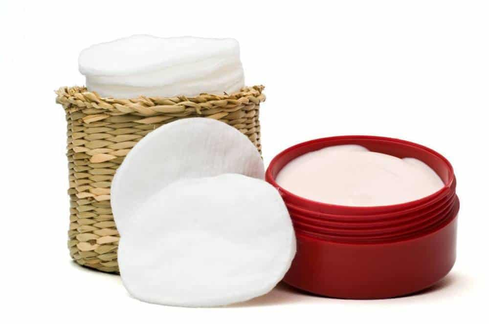 A container of cream with cotton pads.