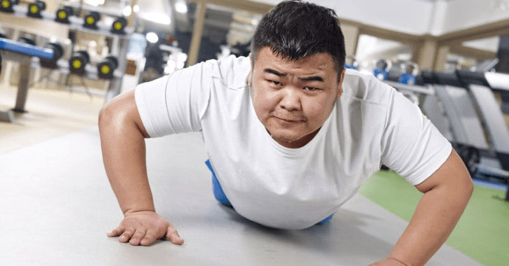 An obese man attempting a push-up in a gym.