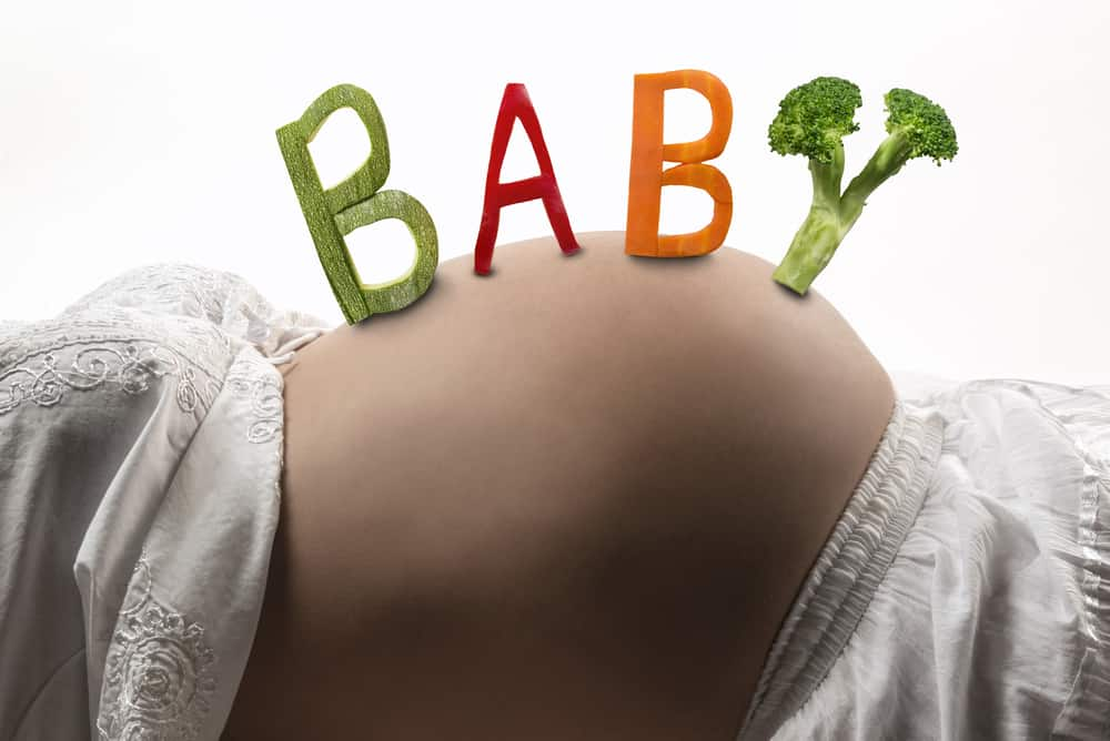 "The word ""BABY"" spelled out by vegetables on a pregnant woman's belly."