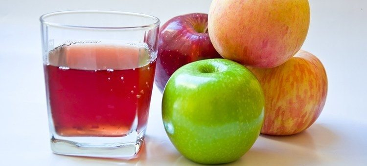 A glass of apple juice next to some apples.