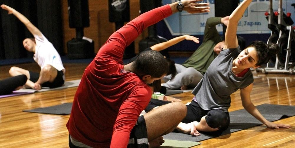 A group of people stretching during a gym exercise.