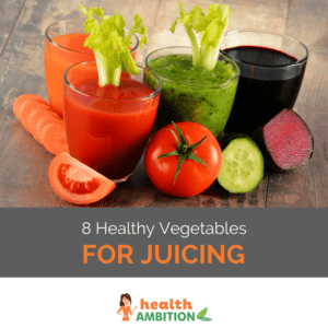 "Glasses of vegetable juice surrounded by vegatables like a slice of tomato, beetroot and a carrot; the title says ""8 Healthy Vegetables for Juicing."""