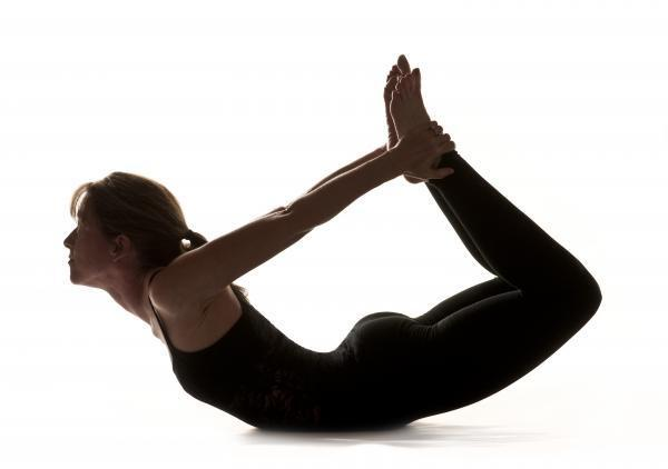 A woman performing the Bow yoga pose.