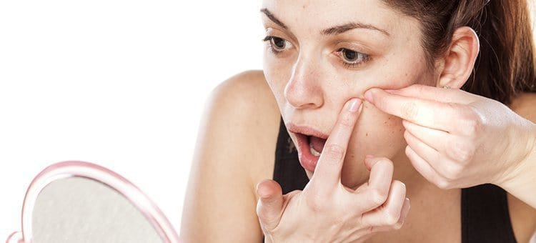 A woman popping her acne in front of a small mirror.