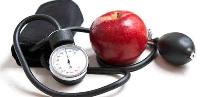 An apple next to a blood pressure monitor.