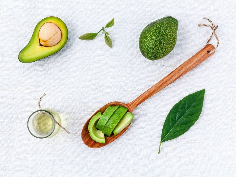 Avocado and leaves with a wooden spoon.