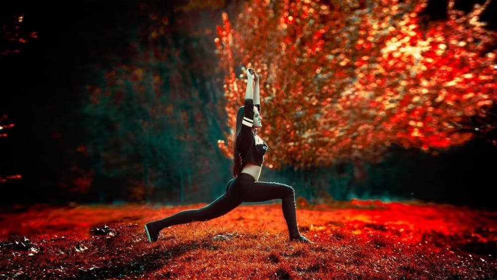 A girl exercising in a forest.