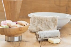 Washcloth and brush next to a bowl of soap.